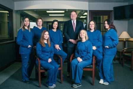 The team at Goebel Family Dentistry. Photo of 6 women smiling and Dr. Goebel smiling.