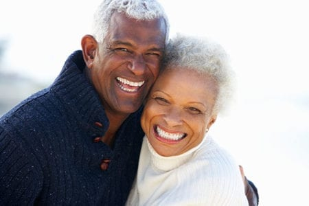 Happy older couple smiling, showing their beautiful white teeth