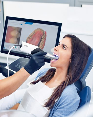 Woman in dental shair getting her teeth scanned for a CEREC same-day crown
