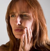 Picture of a toothache patient needing a New Orleans emergency dentist.