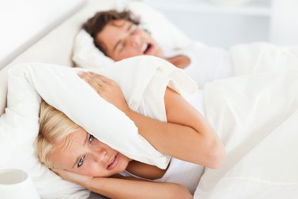 Woman covering her ears with her pillow while her husband snores