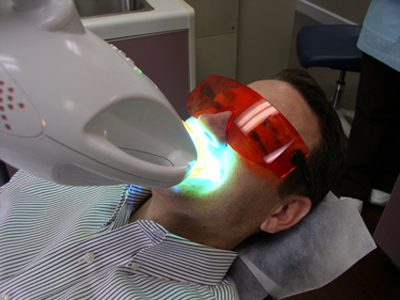 a patient sitting under a Zoom Whitening lamp