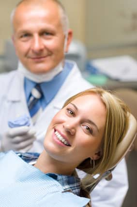 Woman smiling in a dental chair near her dentist
