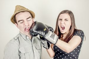 A woman with a boxing glove punching a man in a hat.