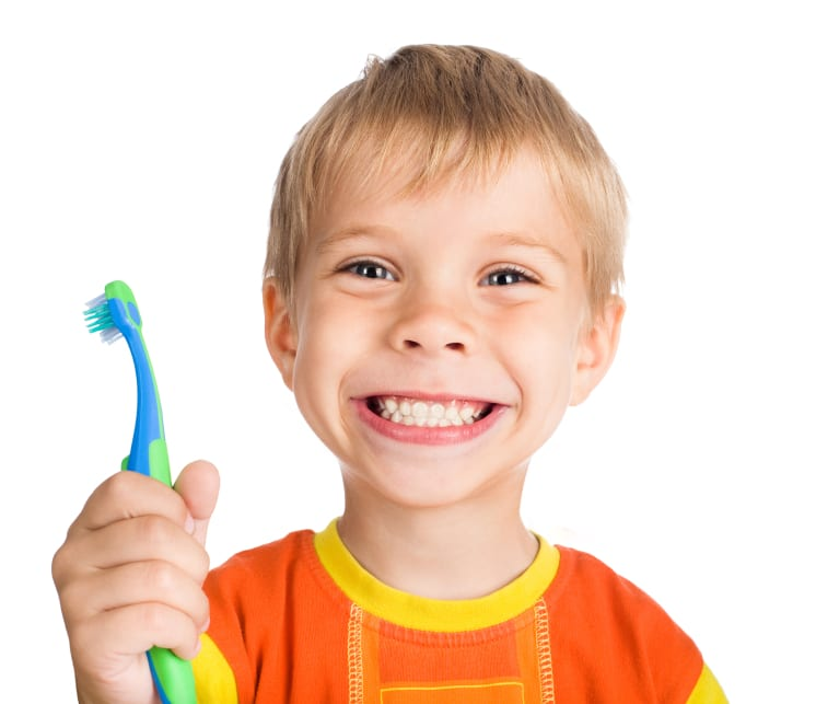 Boy smiling holding a toothbrush